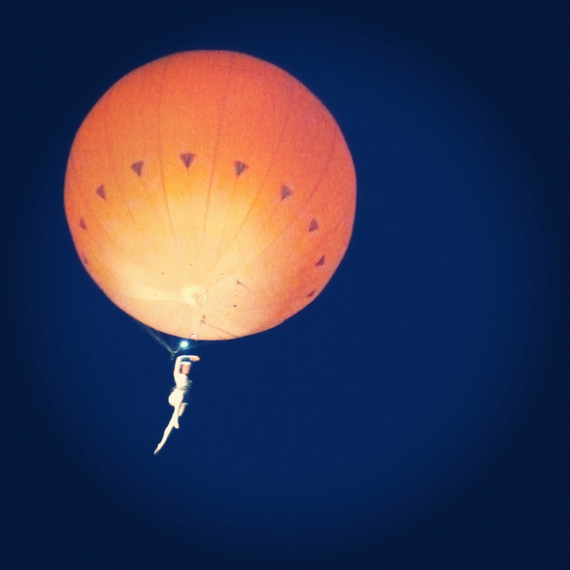 Acrobat dancer attached to a hot air balloon dancing through the sky at Festival Number 6 in Portmeirion Wales