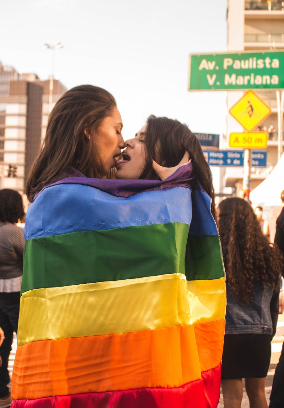two women kissing while wrapped in rainbow flag
